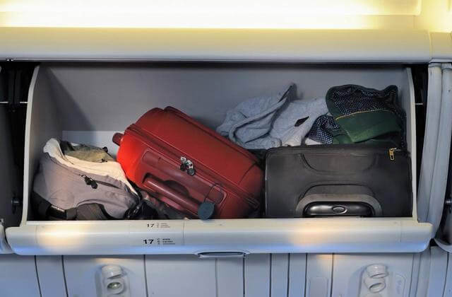cabin luggage in an overhead compartment of a plane