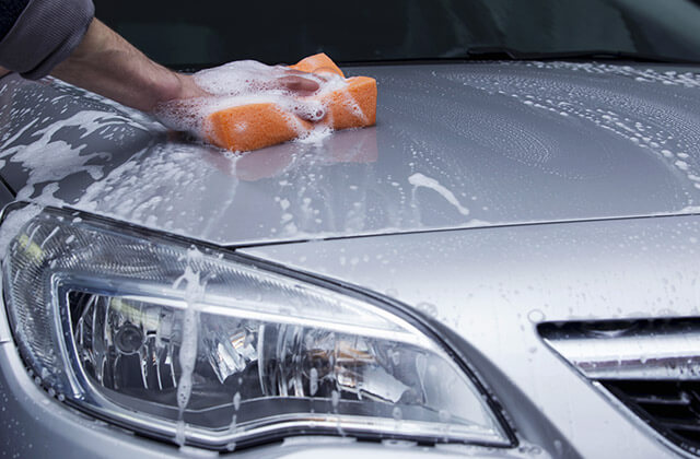 Man cleaning a car with a soft sponge