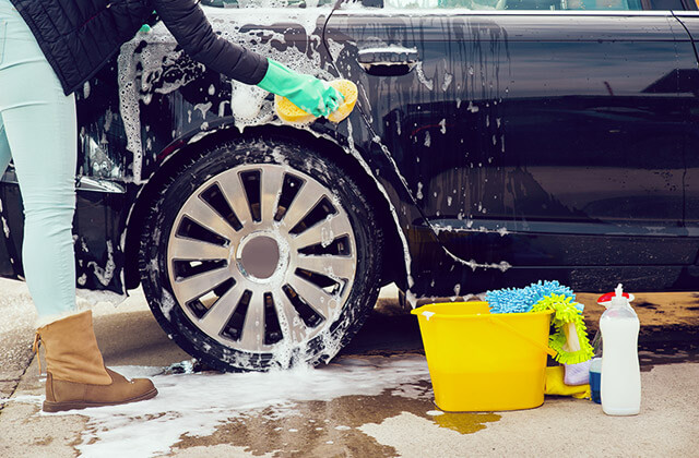 Cleaning the car wheel with a sponge