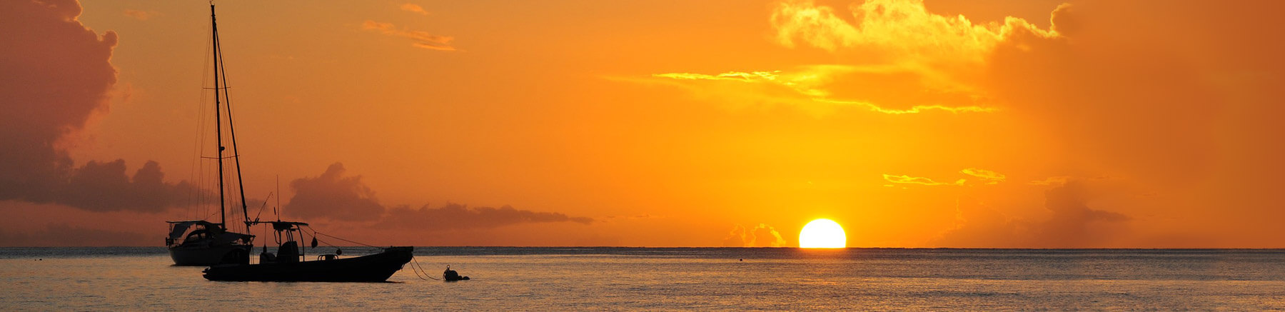 Beautiful sunset in Guadeloupe featuring 2 boats on the sea