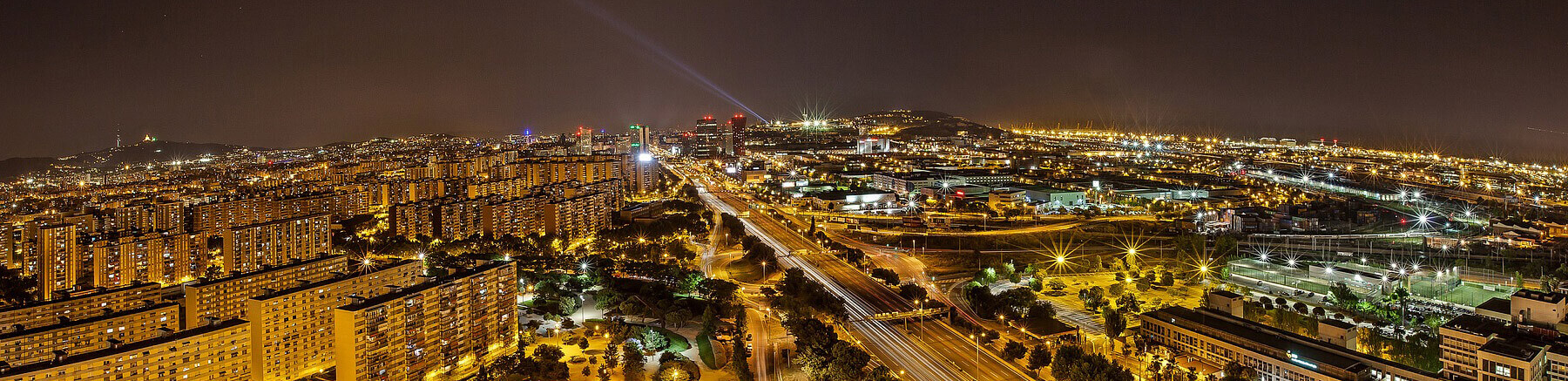 Skyline of Barcelona by night with a lot of lights, residential buildings and highways
