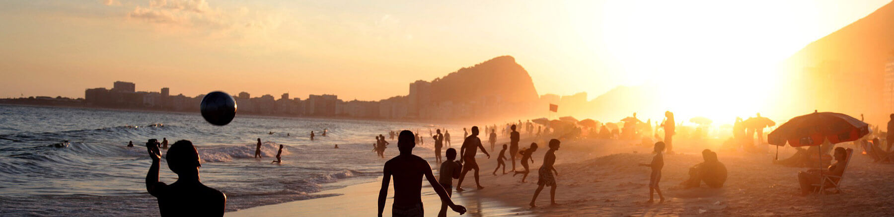 People enjoying Copacabana beach in Rio de Janeiro, Brazil at sunset